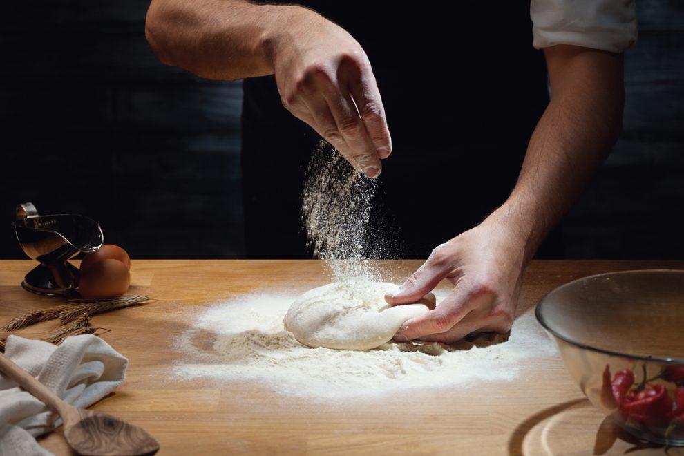 Un pizzaiolo stende la pasta della pizza: lo stendi pizza di Ecor International esegue questa operazione.